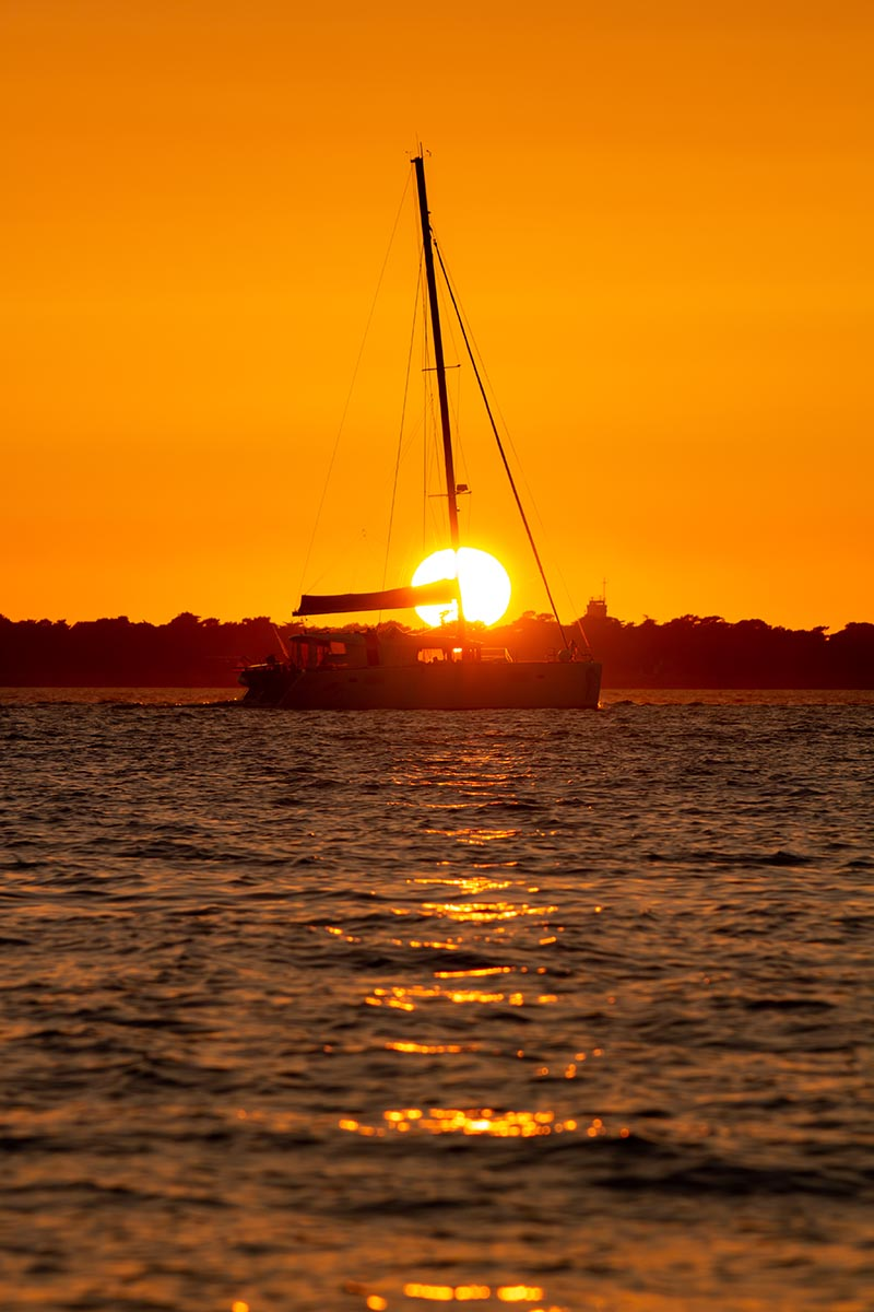Photographie paysage Cap ferret un catamaran entre au port au coucher du soleil