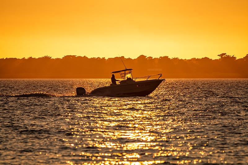 Photographie minimaliste Riki TIki Un homme sur son bateau rentre au port au coucher du soleil