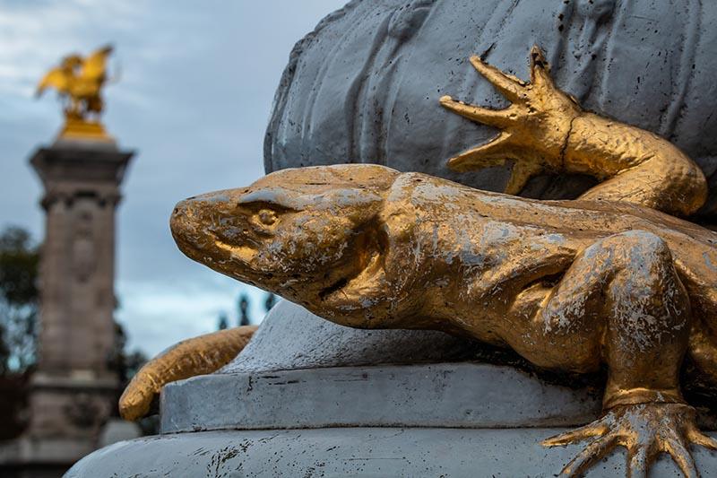 Lézard doré accroché au poteau près du pont Alexandre III