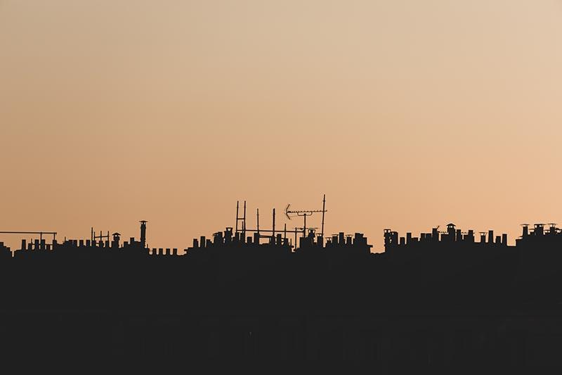Photographie minimaliste Skyline de banlieue la forme des toits qui se dessinent sur fond de soleil couchant